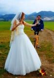 Jeune mariée avec une bouteille à bière et un marié sur la bicyclette sur le fond - concept de mariage Images stock