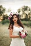Jeune mariée Belle jeune femme blonde en parc avec la guirlande de fleur et bouquet un jour chaud d'été Photos stock