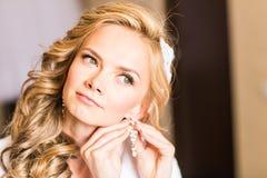 Jeune mariée blonde élégante mettant sur le plan rapproché de boucles d'oreille, se préparant à épouser Photographie stock libre de droits