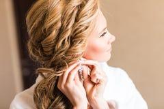 Jeune mariée blonde élégante mettant sur le plan rapproché de boucles d'oreille, se préparant à épouser Photos libres de droits