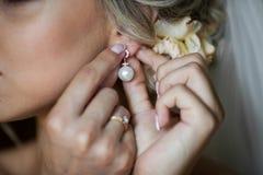Jeune mariée blonde élégante mettant sur le plan rapproché de boucles d'oreille, se préparant à Photographie stock