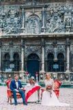 Jeune mariée blonde avec du charme et marié élégant en verres sur le dîner romantique au centre de la ville européenne antique Lv Photographie stock