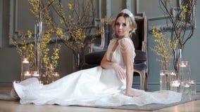 Jeune mariée blonde dans la robe de mariage blanche de mode avec le maquillage clips vidéos