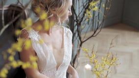 Jeune mariée blonde dans la robe de mariage blanche de mode avec le maquillage banque de vidéos