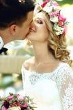 Jeune mariée blonde de sourire heureuse en robe et guirlande blanches embrassant Han Photo libre de droits
