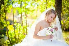 Jeune mariée blonde et le bouquet nuptiale Photos stock