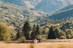 Jeune mariée blonde heureuse dans la robe blanche et le marié se tenant à part près de la haie en bois Image stock