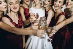 Jeune mariée blonde magnifique élégante heureuse avec des demoiselles d'honneur sur le dos Image libre de droits