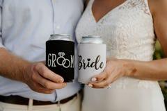Jeune mariée caucasienne enthousiaste et marié Posing tout en montrant la boisson noire et blanche faite sur commande Koozies de  photos libres de droits