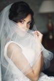 Jeune mariée décontractée sexy de brune se cachant derrière le voile près de la fenêtre blanche Images stock