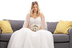 Jeune mariée déprimée assise sur un sofa Image stock