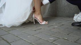 Jeune mariée d'aides de marié pour porter les sandales de robe, chaussures confortables pour des événements, soin banque de vidéos