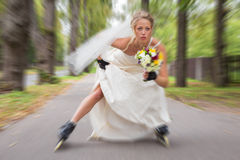 Jeune mariée d'emballement sur des patins de rouleau Images stock