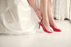 Jeune mariée dans des chaussures rouges Image libre de droits