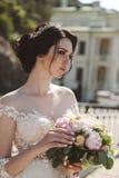 Jeune mariée dans la pose élégante de robe de mariage extérieure avec le bouque tendre photos stock