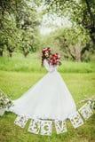 Jeune mariée dans la robe blanche dans un jardin images stock