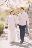Jeune mariée dans la robe blanche de vintage et la chemise de port de marié marchant tenant des mains à la rue de ressort Images stock