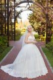 Jeune mariée dans la robe de mariage avec un long train photographie stock
