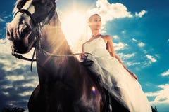 Jeune mariée dans la robe de mariage conduisant un cheval, éclairé à contre-jour Photographie stock libre de droits