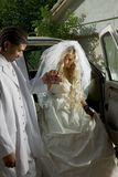 Jeune mariée dans la robe de mariage descendant du véhicule Image libre de droits