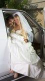 Jeune mariée dans la robe de mariage descendant du véhicule Photographie stock