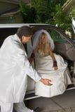 Jeune mariée dans la robe de mariage descendant du véhicule Photo libre de droits