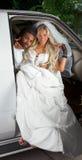 Jeune mariée dans la robe de mariage descendant du véhicule Photo stock