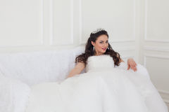 Jeune mariée dans la robe de mariage se reposant sur le divan Photos libres de droits