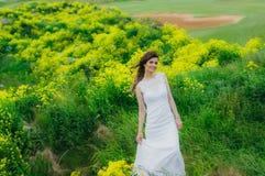 Jeune mariée dans la robe de mariage sur le champ jaune Photo stock