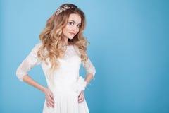 Jeune mariée dans la robe de mariage sur un fond bleu Photographie stock