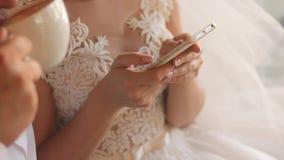 Jeune mariée dans la robe de mariage tenant le smartphone dans des mains Le marié boit du cappuccino banque de vidéos