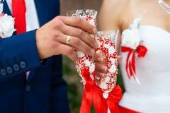 Jeune mariée dans la robe et le marié blancs en verres de tintement de costume bleu-foncé avec de beaux verres faits main à la ta image stock