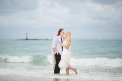 Jeune mariée dans la robe et le marié de mariage étreignant à la mer amour de couples sur la plage abandonnée Images stock