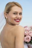 Jeune mariée dans la robe sans dos avec le bouquet de fleur contre le ciel clair Images libres de droits