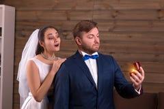 Jeune mariée dans le marié de embrassement de voile avec des anneaux de mariage Photo stock