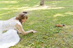 Jeune mariée dans le mensonge blanc sur l'herbe à côté de l'écureuil Image libre de droits