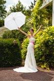 Jeune mariée dans sa robe de mariage blanche avec le parapluie Images libres de droits