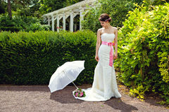 Jeune mariée dans sa robe de mariage blanche avec le parapluie et le bouquet de la Floride Photos libres de droits