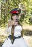 Jeune mariée dans un chapeau de police et une arme à feu Image stock
