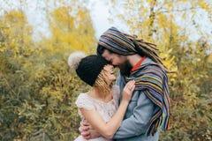 Jeune mariée dans un chapeau tricoté avec un pom de pom, chapeau couvrant ses yeux Marié dans une écharpe colorée Jeunes couples  Image stock