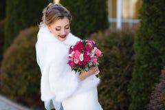 Jeune mariée dans un manteau blanc posant dehors, tenant un bouquet lumineux des fleurs dans des ses mains La fille a abaissé ses Images libres de droits
