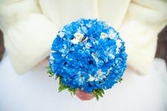Jeune mariée dans un manteau de fourrure tenant un bouquet qui se trouvent des anneaux de mariage Images stock