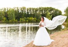Jeune mariée dans une robe blanche avec le bouquet de mariage au lac photographie stock libre de droits