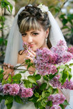 Jeune mariée dans une robe blanche sur un fond lilas au printemps Photo libre de droits