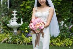 Jeune mariée dans une robe blanche tenant le bouquet de mariage des fleurs avec des rubans image libre de droits