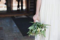 Jeune mariée dans une robe blanche tenant un bouquet des fleurs et de la verdure pourpres sur le fond de l'herbe verte Photo stock