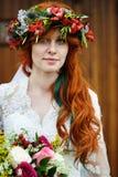 Jeune mariée de Boho avec les cheveux rouges avec des fleurs Images stock
