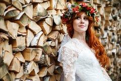 Jeune mariée de Boho avec les cheveux rouges avec des fleurs Photographie stock