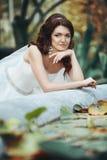 jeune mariée de brune posant près du plan rapproché rustique de fontaine Photographie stock