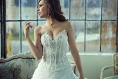Jeune mariée de brune se reposant après réception de mariage Images stock